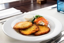 Traditional Belarus potato pancakes (draniki) with sour cream in a plate at a cafe